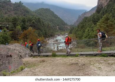 Nepal, Phakding - April 23, 2019: Travelers crosses Dudh Koshi river near Phakding village on the suspension bridge on the way to Everest base camp, Solukhumbu, Nepal. Travel and tourism concept.