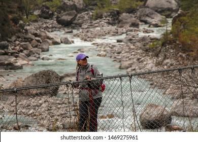 Nepal, Phakding - April 23, 2019: Traveler crosses Dudh Koshi river near Phakding village on the suspension bridge on the way to Everest base camp, Solukhumbu, Nepal. Travel and tourism concept.