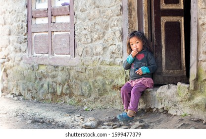 "Nepalese little girl portrat in ""I love Nepal"" shirt looking curios at the viewer with hand at mouth sitting on treshold with open door of the traditional stone house in Lukla, Nepal, 14 October 2016"