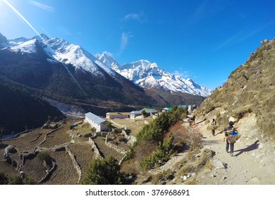 Nepalese porter (sherpa), low paid hard and dangerous job, trekking in Himalaya scenery, peaceful landscape with fields and valley on sunny summer day, small mountain village, trek to Everest, Nepal