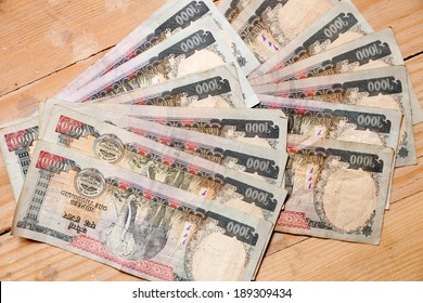 Nepalese thousand rupee banknotes on a yellow wooden underground