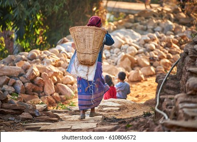 Nepalese woman carries huge wicker basket on her back at the street of Bandipur, Nepal.