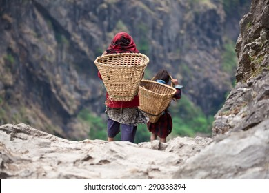 Nepali children in national clothes with baskets on mountain path