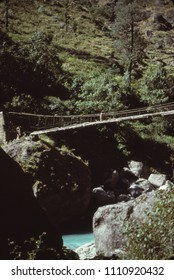Nepali crossing high supension bridge in the Rowaling Himalaya, Nepal, Asia