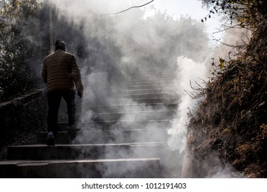 A Nepali man walking on the step to the top of mountain inside the smoke of dry grass burning.