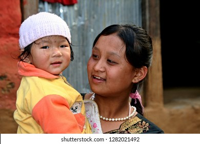 Nepali native young girl with kid. Bhulbhule village. 23th March 2009. Nepal. Asia.