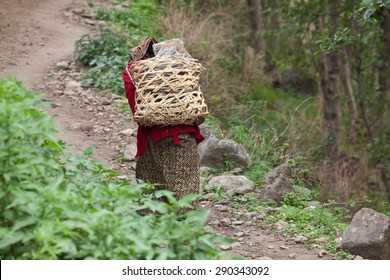 Nepali woman in national clothes with baskets on mountain path