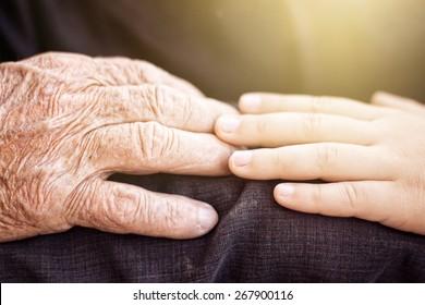 nephew touching grandfather's hand in sunlight