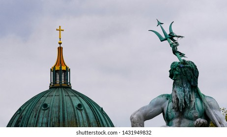 Neptune Fountain and Berliner Dom. Famous fountain on Alexanderplatz.  Part of fountain presenting sculpture of god Neptune but the background is the roof of the cathedral with a golden cross.