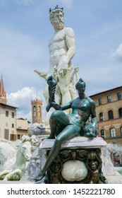 Neptune fountain in Florence. Neptune made of white marble, in front of Neptune bronze figure of water. Behind Neptune visible water and horses. Italy
