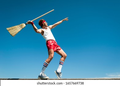 Nerd athlete throwing broom as javelin in his own special version of a track and field event