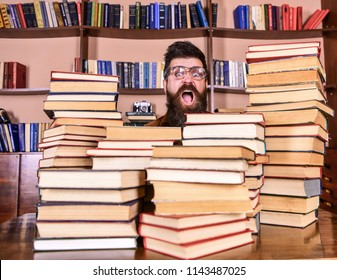 Nerd concept. Teacher or student with beard wears eyeglasses, sits at table with books, defocused. Man, nerd on surprised face between piles of books in library, bookshelves on background.