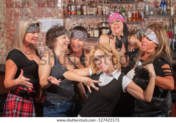 Nerd flexes muscles for tough female gang in bar