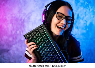Nerd geek young adult women holding gaming keyboard over colorful pink and blue neon lit wall. Gaming gamers concept.