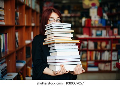 Nerd girl with eye glasses holding bunch of books in library