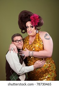 Nerd hugs a large large drag queen over a green background