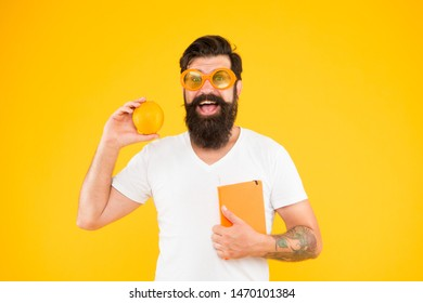 Nerd is the new cool. Bearded nerd man. Study nerd holding book and orange fruit on yellow background. Book nerd in fancy glasses choosing natural diet.