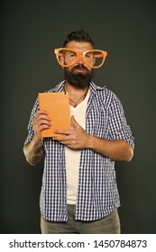 Nerd is the new cool. Study nerd holding book. Book nerd wearing fancy glasses. University male student with lecture notes. Bearded man in party glasses with lesson book.