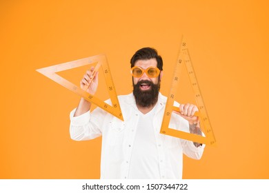 Nerd succeeded in proving the theorem. Happy nerd. Study nerd holding triangles on orange background. Bearded man in fancy nerd glasses making technical drawing.