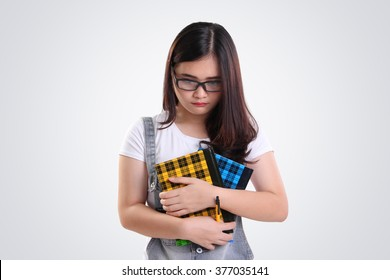 Nerdy Asian school girl looking down with sad depressed face, on white background