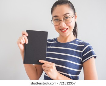 Nerdy Asian woman smiles and holding a good book.