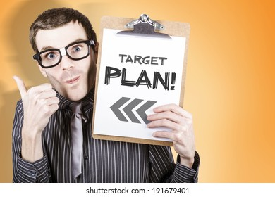 Nerdy businessman gesturing thumb up with clipboard and written target plan