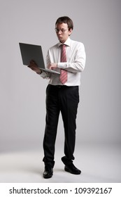 Nerdy businessman holding a laptop and making a face