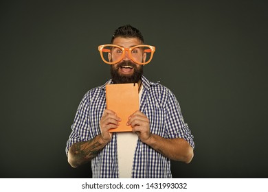 Nerdy and funny. University male student with lecture notes. Study nerd holding book. Book nerd wearing fancy glasses. Bearded man in party glasses with lesson book.