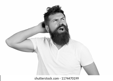 Nerdy, idiot, dork, fool scratching head in deep thought, daydreaming. Man with beard and mustache yawning while scratching, isolated on white background. Guy drowsy with tousled hair. Morning concept