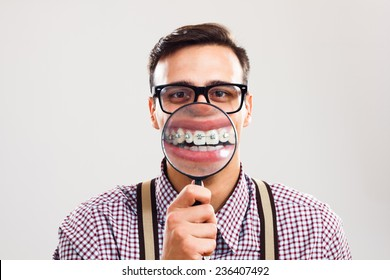 Nerdy man is holding loupe and showing his teeth with braces.I have braces and I am still handsome!