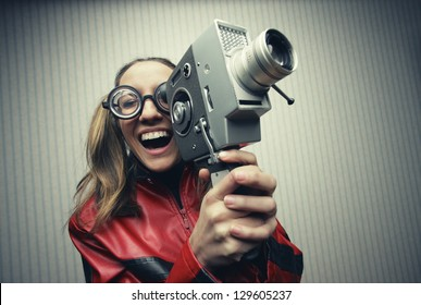 Nerdy woman using old fashioned cine camera