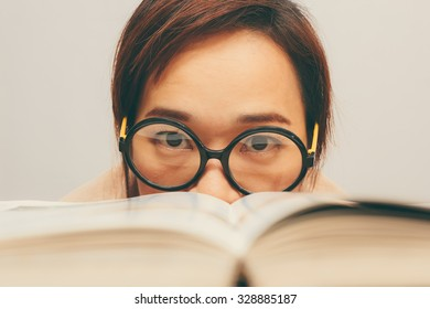 Nerdy young asian woman student with old big round glasses bored with reading book + vintage filter