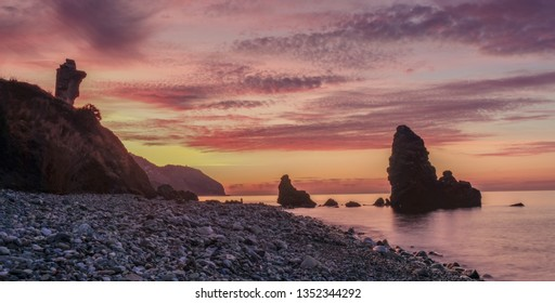 Nerja, Malaga, Andalusi, Spain - February 7, 2019: Molino Beach, small stone beach with two large rocks on the shore, Nerja, southern Spain