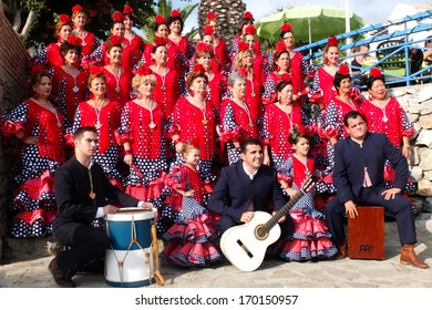 NERJA, SPAIN -  OCTOBER 6:  Some women wearing traditional dresses, two little girls and three musicians from an Andalusian folk group are posing for a photo, on October 6, 2013, in Nerja, Spain.