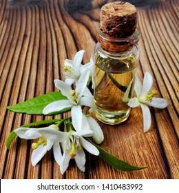 Neroli (Citrus aurantium) essential oil in bottle. Fresh white flowers, green leaf & neroli essential oil. Natural citrus flower attar perfume (neroli essential oil) for aromatherapy, spa, massage.
