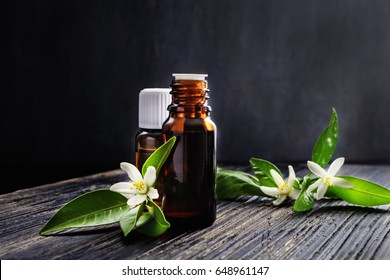 Neroli (Citrus aurantium) essential oil in a brown glass bottle with fresh white  flowers on old black textured wooden background.  Copy space, Selective focus.