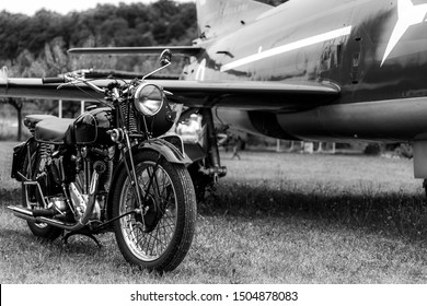 Nervesa della Battaglia, Italy - 07/2017: Old, black motorcycle made by Triumph Motorcycles - british brand with a blue airplane in the background. Black and white.