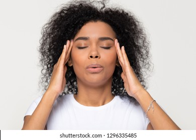 Nervous african woman breathing calming down relieving headache or managing stress, black girl feeling stressed self-soothing massaging temples exhaling isolated on white grey studio blank background