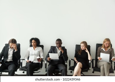 Nervous applicants preparing for employment interview sitting on chairs in queue row line, african and caucasian diverse unemployed people feeling stressed about tedious waiting, job hunting concept