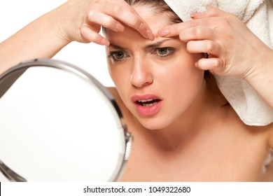 Nervous beautiful woman with towel on hr head on white background squeeze pimples on her face