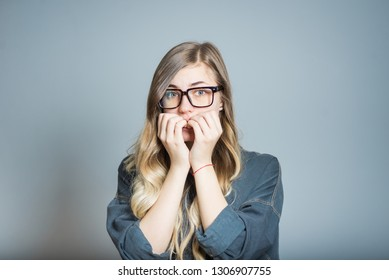 Nervous blond girl biting nails and worried, isolated on a gray background