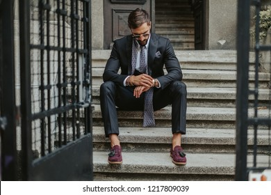 Nervous businessman waiting on the stairs in daytime and looking at the time