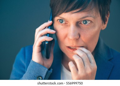 Nervous businesswoman bites fingernails during telephone conversation on mobile phone