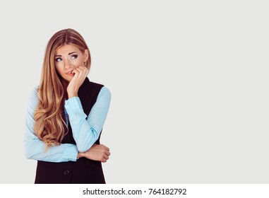 Nervous. Closeup portrait head shot stressed young woman girl employee student biting fingernails looking anxiously craving something over light grey background. Human emotion face expression feeling
