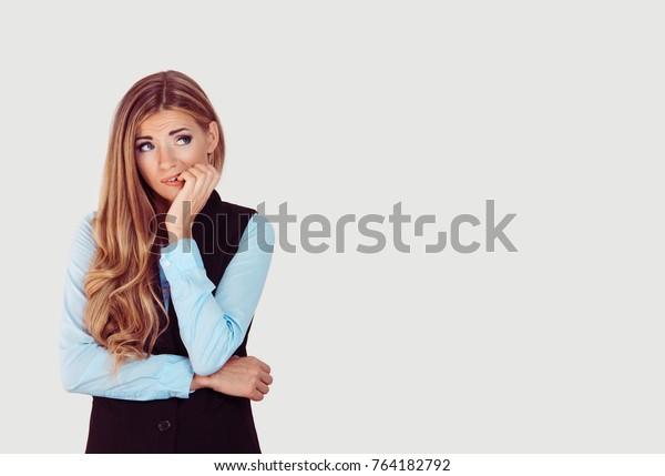 緊張して。薄いグレイの背景に何かを欲しがる若い女性の女の子の女の子の女の子の女の子学生が、不安そうに爪をかみながらストレスを感じた、接写の頭のショット。人間の感情的な顔の表情