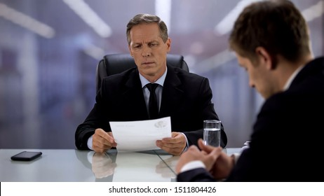 Nervous employee waiting for boss reading curriculum vitae, hoping for best