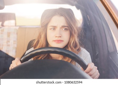 Nervous female driver sits at wheel, has worried expression as afraids to drive car by herself for first time. Frightened woman has car accident on road. People, driving, problems with transport