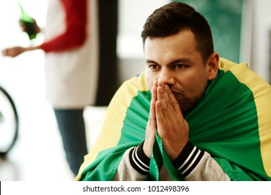 Nervous football fan with flag praying