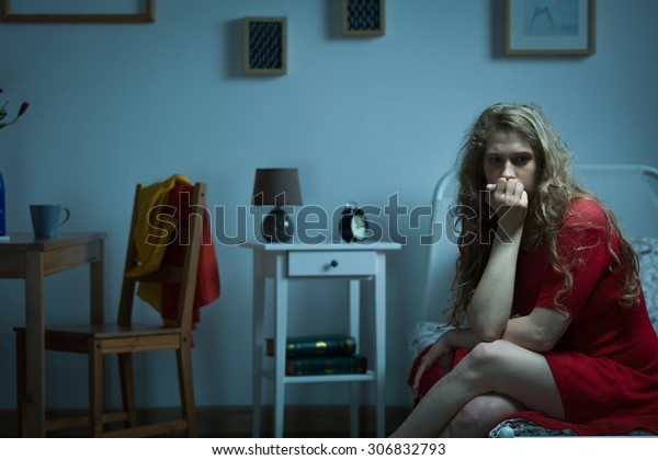 Nervous girl sitting on the bed and biting nails