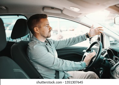 Nervous handsome Caucasian man getting stacked in traffic while driving his car.